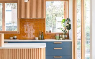 kitchen, grey floor tiles, wooden slats on curvy island, wooden slats on upper cabinet, blue bottom cabinet, white kitchen top, brown backsplash tiles, wooden shelves