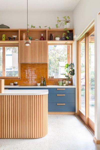 kitchen, grey floor tiles, wooden slats on curvy island, wooden slats on upper cabinet, blue bottom cabinet, white kitchen top, brown backsplash tiles, wooden shelves
