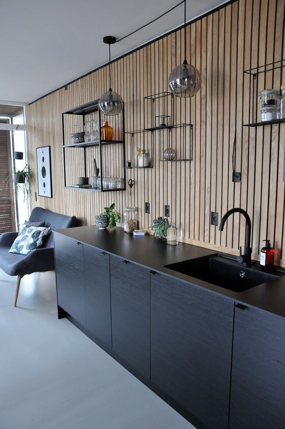 kitchen, grey seamless floor, black bottom cabinet, woden slats wall, floating wire shelves, grey sofa, clear glass bulb pendants