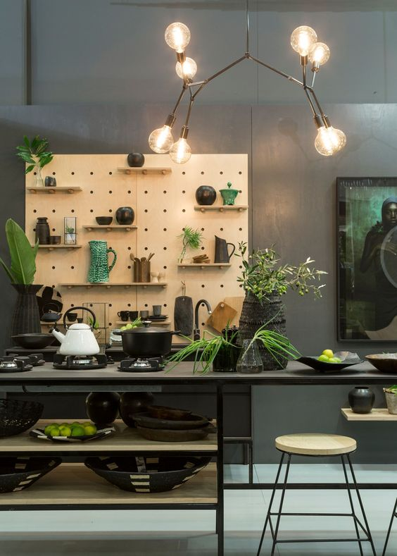 kitchen, off white floor, black table shelves, black stool, wooden pegboard, bulb chandelier, dark grey wall