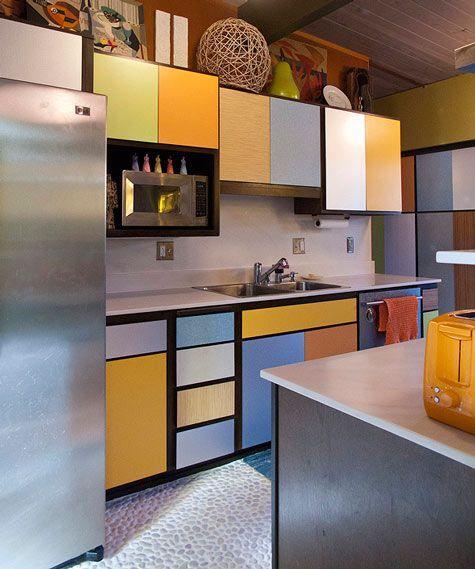 kitchen, off white floor, grey backsplash, colorful doors on cabinet, white kichen top, grey island