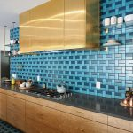 Kitchen, Patterned Blue Tiles On Wall And Floor, Wooden Cabinet, Black Kitchen Top, Golden Upper Cabinet, Glass Floating Shelves