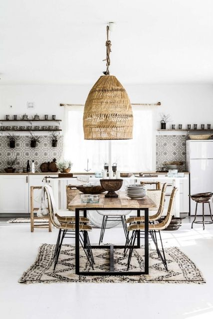kitchen, white floor tiles, white rug, wooden dining set with lack metal legs, white bottom cabinet, white wall, black white backsplash, rattan pendant, open shelves