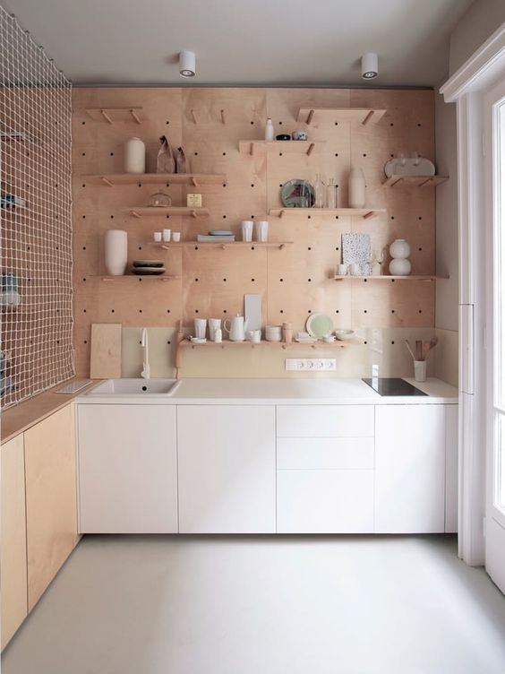 kitchen, white floor, white bottom cabinet, brown bottom cabinet, wooden pegboard wall with shelves, sink