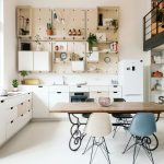 Kitchen, White Floor, White Wall, White Cabinet, White Fridge, Wooden Dining Table With Pink, Black, Blue Chairs, Wooden Pegboards For Shelves And Cabinet On The Wall