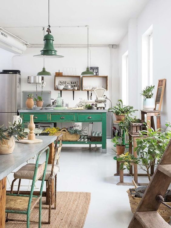 kitchen, white floor, wooden table with silver top, colored metal chairs, green wooden island, white wall, green pendants, grey cabinet