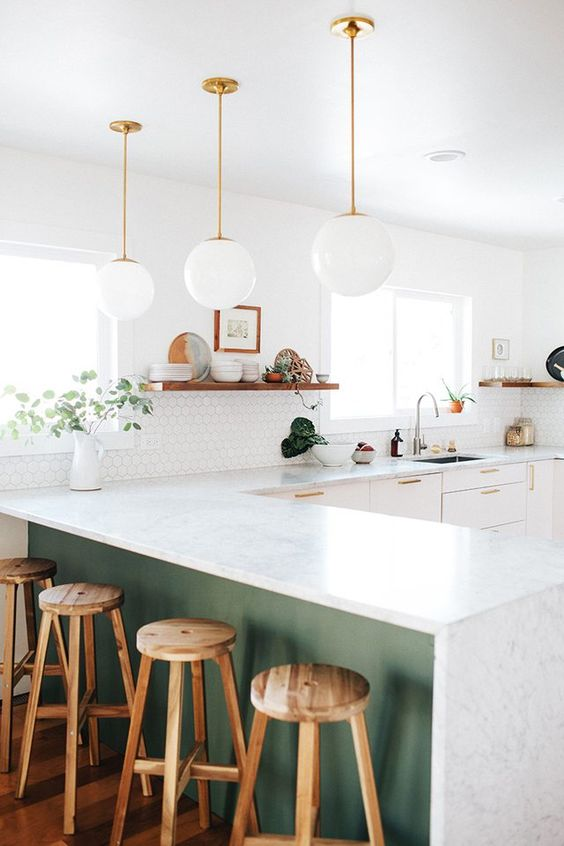 kitchen with white marble top, white cabinet, white hexagonal wall tiles, white ball pendants, green under the kitchen island, wooden stool