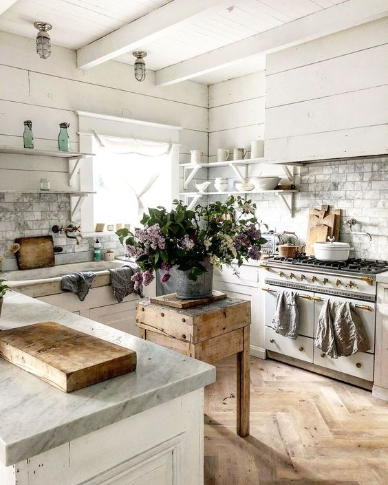 kitchen, wooden chevron floor, white wooden bottom cabinet, white wooden wall and ceiling, wooden small table, white wooden floating shelves