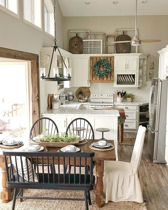 kitchen, wooden floor, rattan rug, wooden table with black chairs and bench, white wall, white bottom cabinet, white upper cabinet