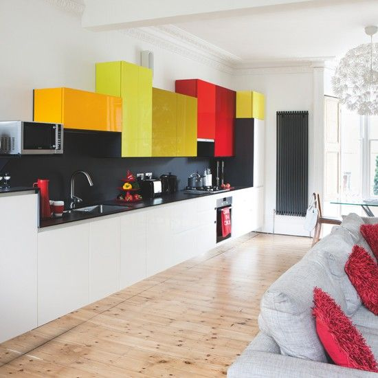 kitchen, wooden floor, white bottom cabinet, black backsplash wall, black kitchen top, orange yellows red upper cabinets