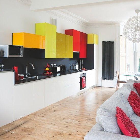 kitchen, wooden floor, white bottom cabinet, black backsplash wall, black kitchen top, orange yellows red upper cabinets