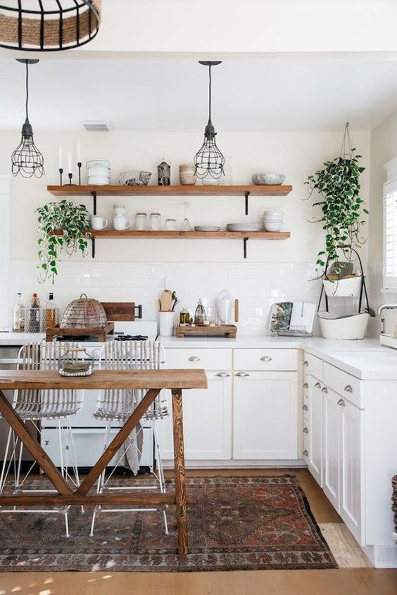 kitchen, wooden floor, white bottom cabinet, white backsplash tiles, white wall, open shelves, wooden table with wired chairs, wired pendants
