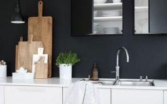 kitchen, wooden floor, white cabinet, black wall, black built in upper cabinet, black pendant, white top