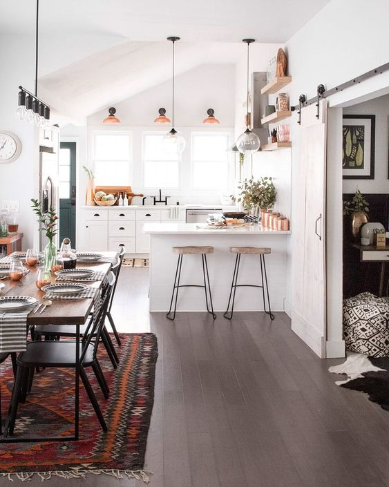 kitchen, wooden floor, white cabinet, white wall, three windows, three sconces, clear glass pendant, white top, wooden stool, floating shelves