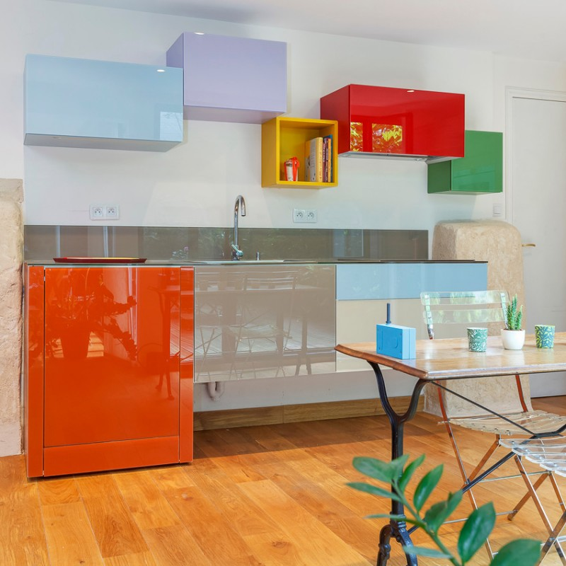 kitchen, wooden floor ,white wall, glossy orange blue grey bottom cabinet, glossy blue grey red green shelves, yellow shelves, table