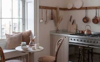 kitchen, wooden floor, white wall, wooden bottom cabinet, grey marble top, wooden round table, wooden chairs, window bench, pendant