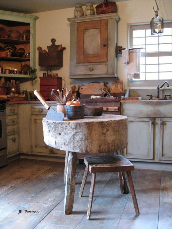 kitchen, wooden floor, white washed out bottom cabinet, white wall, wooden top, wooden floating shelves, pendant, round wood slab table with stool