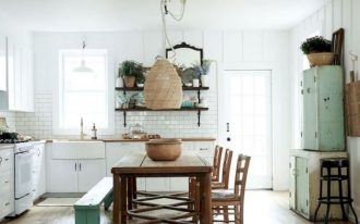kitchen, wooden floor, wooden dining set with green bench, white plank wall, white subway backsplash wall, white bottom cabinet, white apron sink, green cabinet, rattan pendant