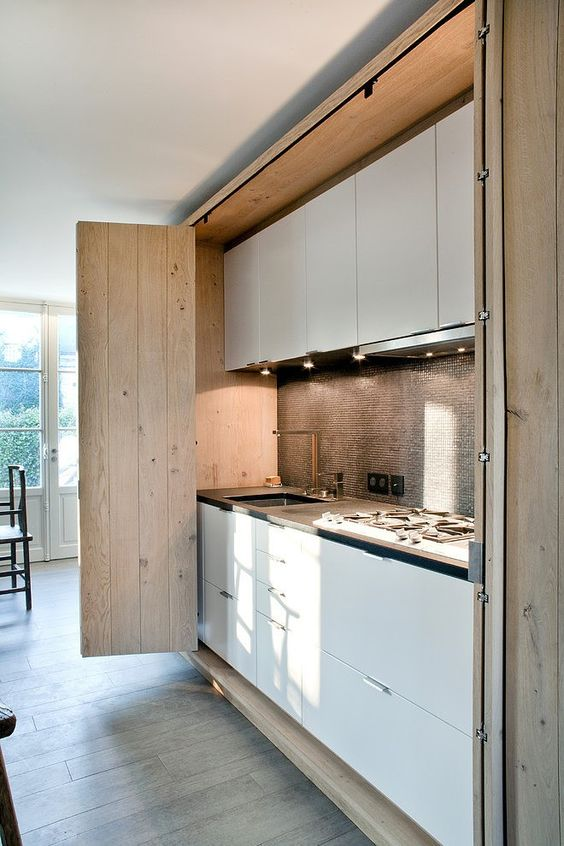 kitchen, wooden floor, wooden folding door with white upper and bottom cabinet, backsplash