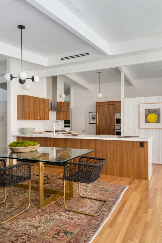 kitchen, wooden floor, wooden kitchen cabinet with white top, white wall, woden pantry, pendant, glass dining table, black rattan chairs