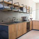Kitchen, Wooden Floor, Wooden Slats Bottom Cabinet, Black Top, Seamless Grey Wall, Floating Shelves