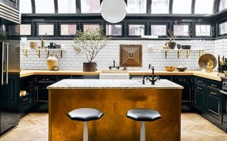 kitchen, wooden herringbone floor, golden island with marble top, black bottom cabinet, white subway blacksplash, curve glass ceiling, white glass pendant, black stool