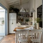 Kithen, Wooden Floor, White Wall, White Kitchen With Open Shelves, White Fridge, White Pendants, Wooden Dining Table With White Chairs