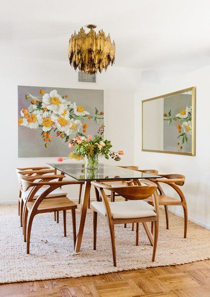 lean wooden chairs with curve, glass top table with wooden legs, copper chandelier, wooden floor, rattan rug, white wall