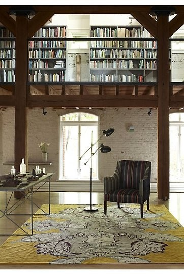 lighting floor lamps glass railing black armchair yellow patterned area rug industrial desk wooden beas bookshelves glass doors