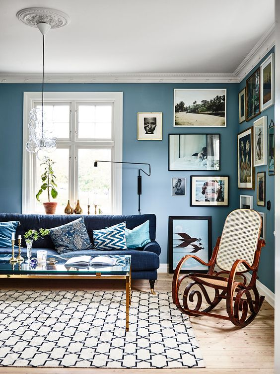 living room, wooden floor, blue wall, white ceiling, glass pendant, blue sofa, wooden rocking chair, white rug, glass top coffee table