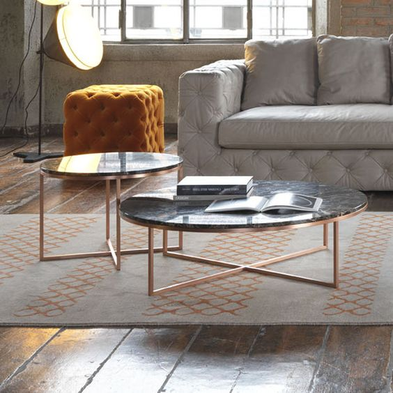 living room, wooden floor, grey rug, black round marble nesting table with copper cross legs, gey tufted sofa, orange tufted ottoman