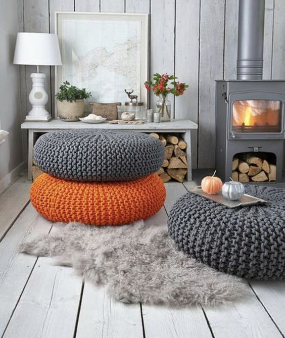 living room, wooden floor, wooden wall, grey metal fireplace, grey orange ottoman, wooden table, woods under