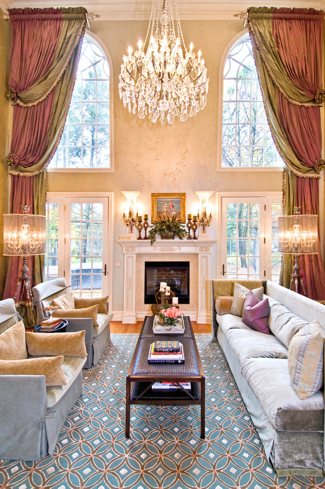 luxurious living room crystal chandelier coffee table gray sofa blue armchairs area rug fireplace wall sconces floor lamps red drapes glass windows