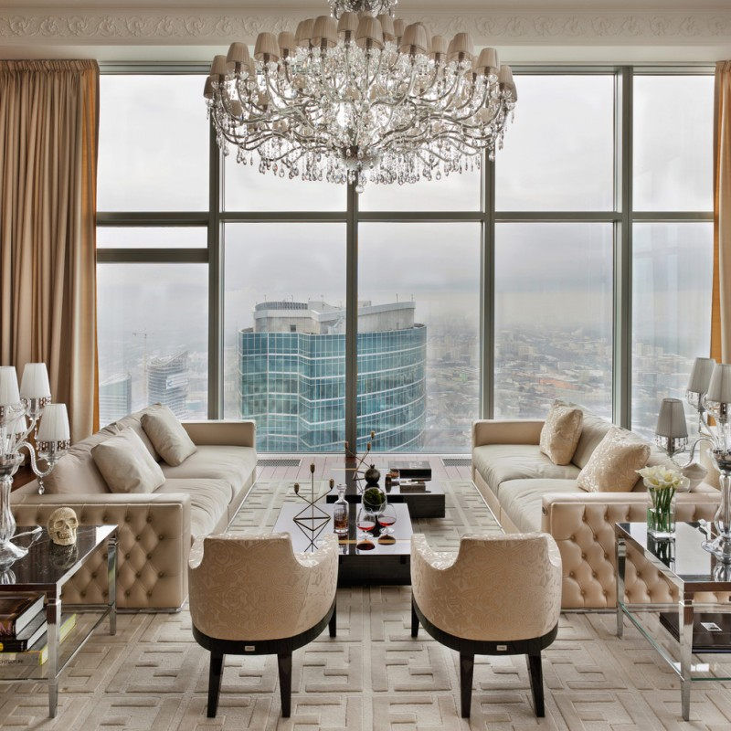 luxurious living room crystal chandelier large glass windows beige sofas beige armchairs beige textured carpet glass side tables beige curtains blak glass coffee table