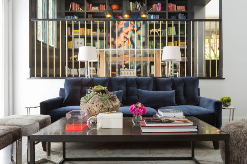 modern blue couch brass railing black coffee table glass table lamps white shades gray stools brown shag ottoman blue pillows