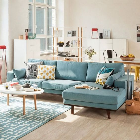 modern living room, wooden floor, blue rug, blue cornered sofa, white wall, white cabinet, shelves