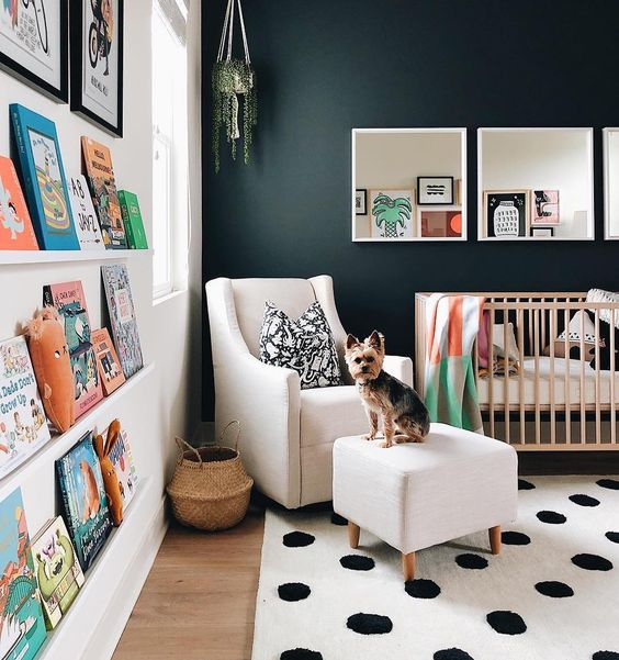 nursery, wooden floor, polka dot rug, floating display shelves, dark gree wall, white wall, wooden crib, white chair with ottoman