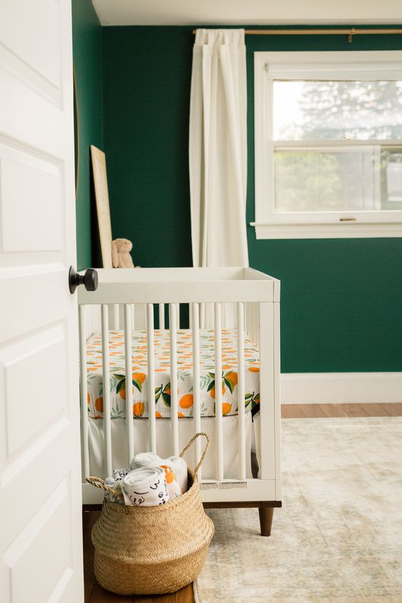 nursery, wooden floor, rug, white crib, dark green wall, white wooden framed window, white curtain