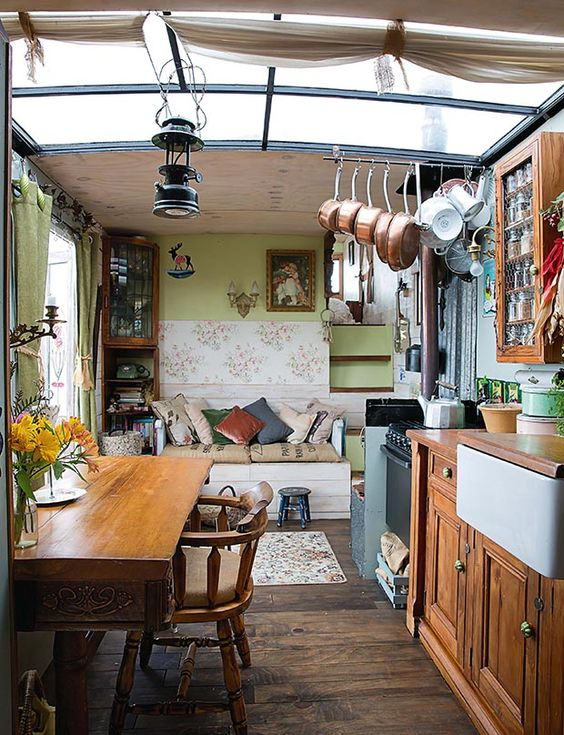 open room, kitchen with wooden bottom cabinet, apron sink, floating wooden shelevs, wooden table, wooden chair, lliving room with green wll, white bench with cushion and pillows