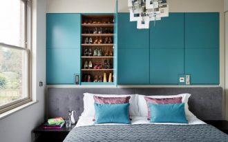 over bed lighting blue cabinet shoe storage gray headboard low bedside tables blue and purple pillows white bedding windows