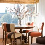 Pedestal Dining Table With Leaf Bamboo Shade Glass Windows White Curtain Colorful Dining Chairs Glass Flower Vase Brown Flooring