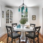 Pedestal Dining Table With Leaf Blue Chandelier Wooden Floor Black Chairs White Walls Window White Corner Cupbiard
