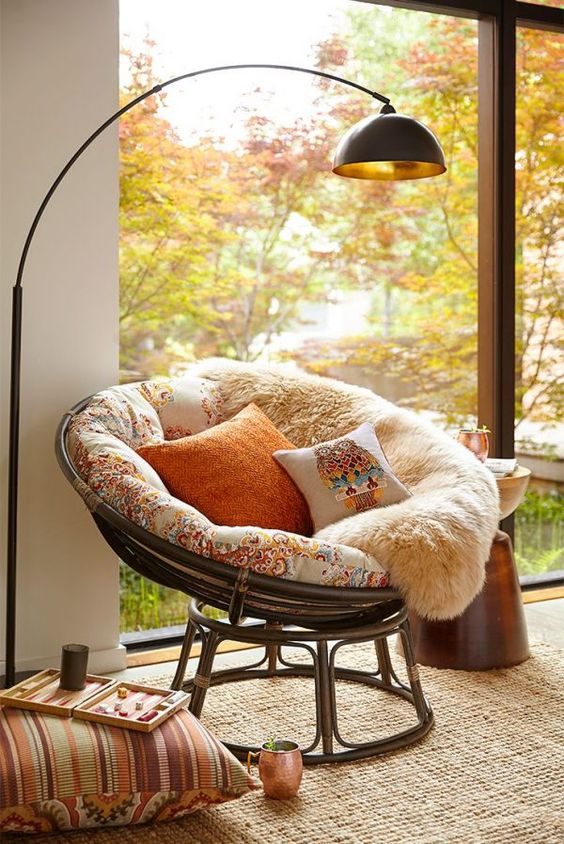 rattan frame with flowery cushion, fur blanket, floor lamp, rattan rug, side table