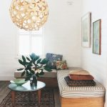 Round Rattan Pendants, Living Room With White Planks On The Wall And Ceiling, Wooden Bench With Striped Cushion, Black Round Coffee Table, Dark Patterned Rug