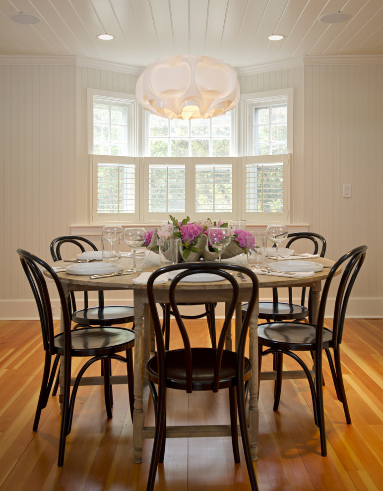 rustic dining table white chandelier white windows wooden pedestal table dark brown chairs wooden floor shutter