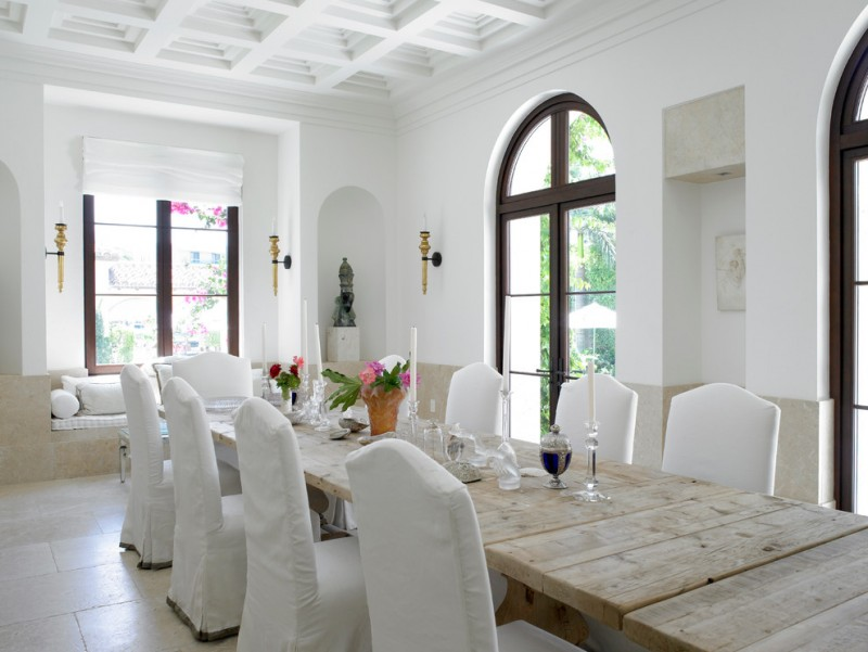 rustic dining table white tray ceiling wall sconces white skirt chairs arched glass doors glass windows white shade window seat