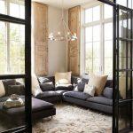 Singular Chandelier, Wooden Floor, Dark Grey Corner Sofa, Glass Partition, Large Window