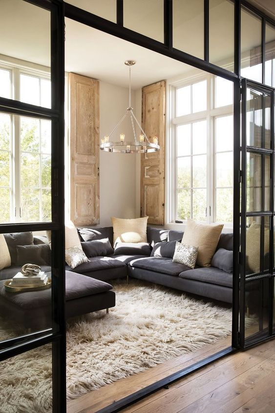 singular chandelier, wooden floor, dark grey corner sofa, glass partition, large window