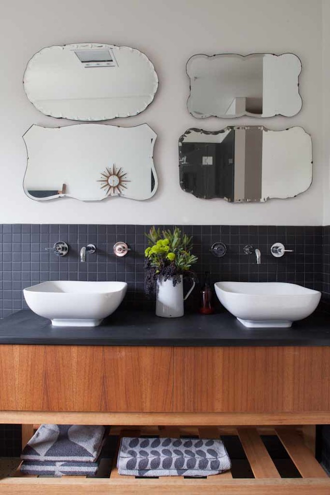 sink bowl wall mounted faucet black backsplash wooden vanity black top antique wall mirrors white wall flower vase towels
