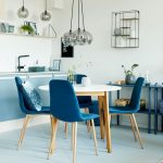 Smal Open Kitchen With Blue Cabinet, Blue Floor, White Wall, Silvery Bulb Pendant, Blue Shelves, Blue Chairs With Wooden Legs, White Round Table With Brown Woden Legs